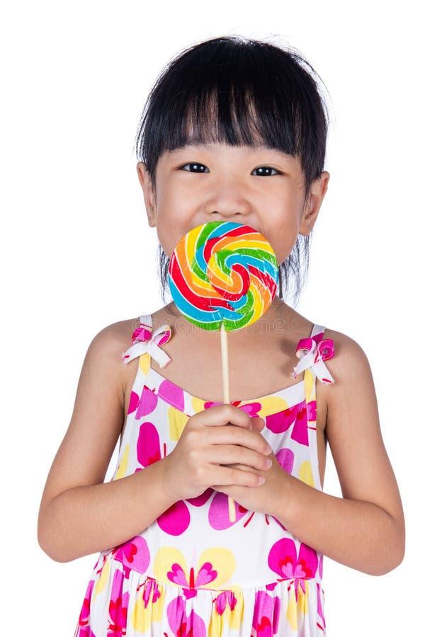 吃棒棒糖的亚裔矮小的中国女孩 免版税库存照片