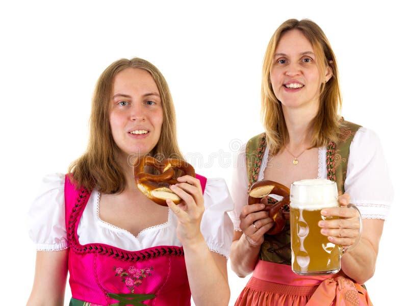 吃椒盐脆饼和喝在oktoberfest的啤酒 免版税库存图片