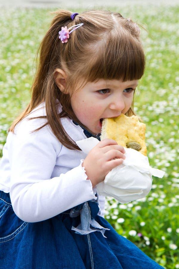 吃橄榄小圆面包的小美丽的女孩 图库摄影
