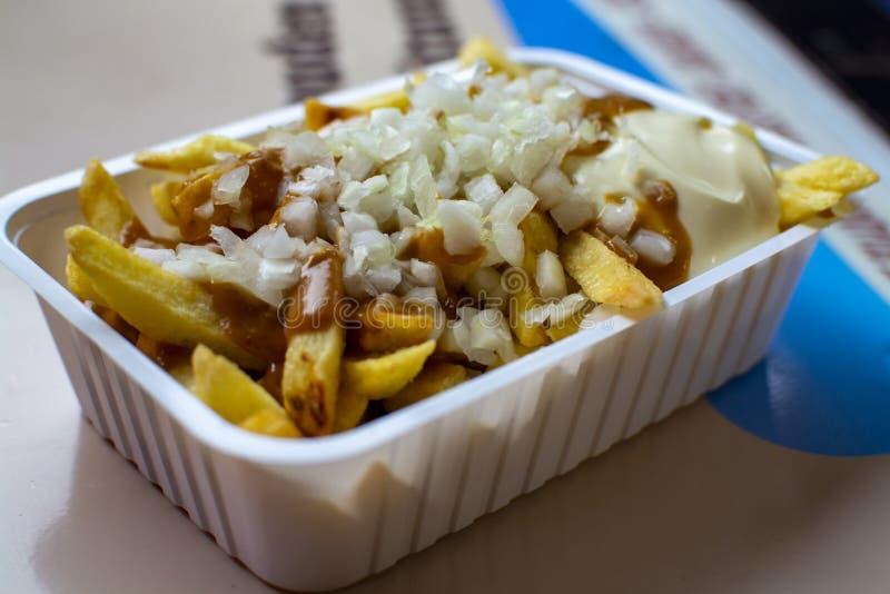 吃比利时油煎的potatos芯片用葱,心满意足和蛋黄酱,街道便当 免版税库存照片