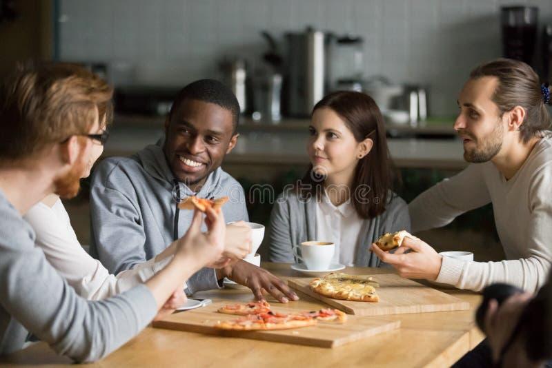 吃比萨享受有趣的谈话的不同的朋友在桌上 免版税库存照片