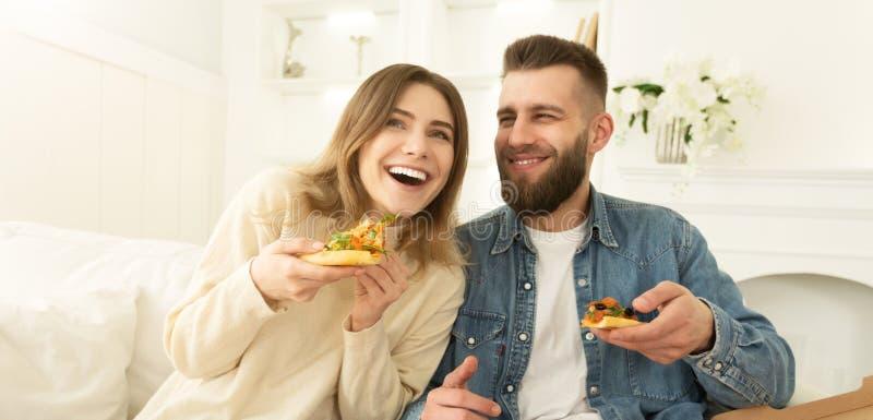 吃比萨和嘲笑家的愉快的夫妇 库存照片