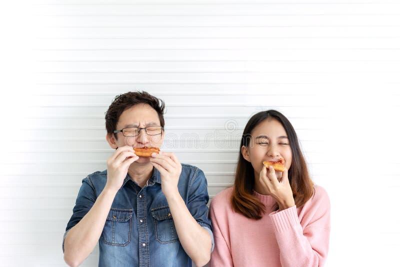 吃比萨或便当与微笑和鲜美表情的有吸引力的亚洲饥饿的夫妇在面孔有白色墙壁背景 库存图片