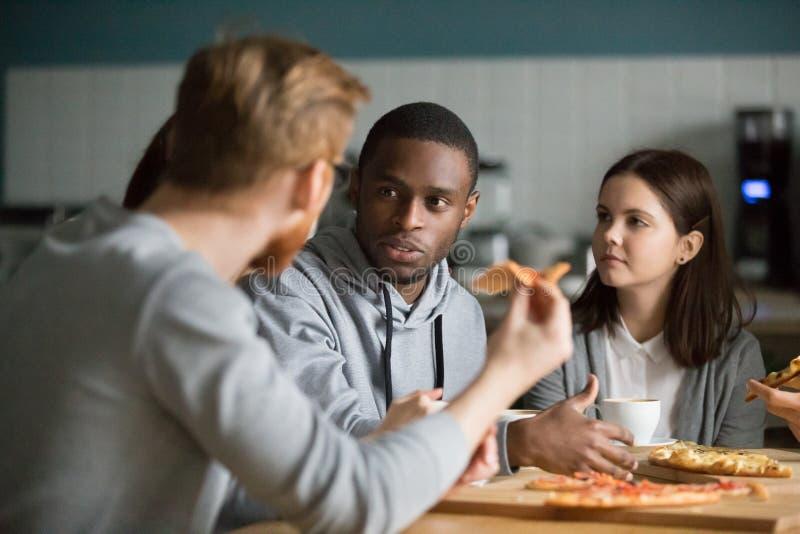 吃比萨的不同的年轻人放松在比萨店 图库摄影