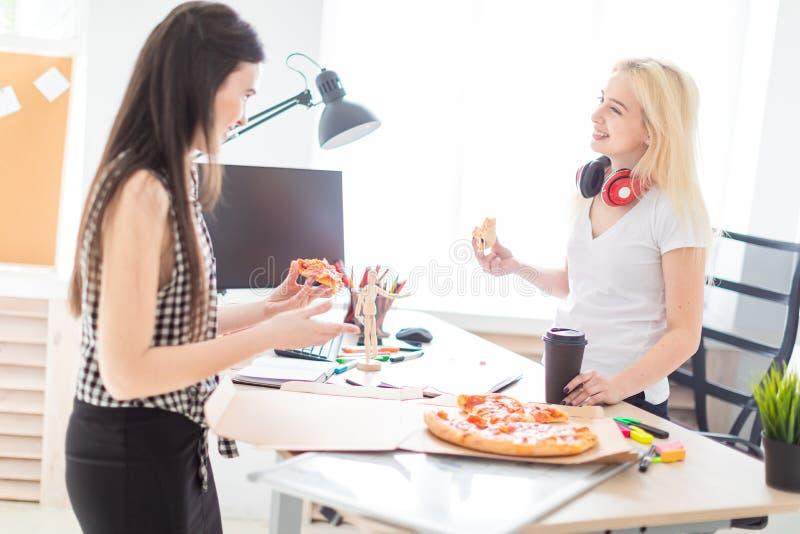 吃比萨的两个女孩在办公室 免版税图库摄影