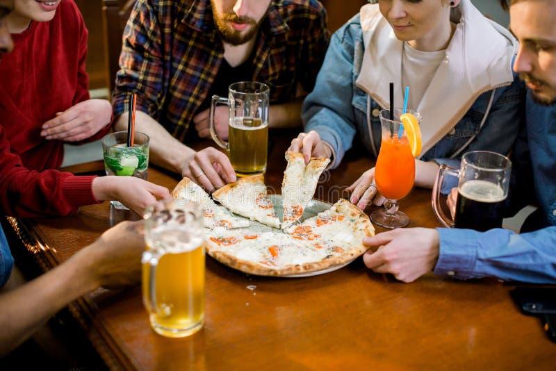 吃比萨的多种族愉快的年轻人在比萨店,笑快乐的朋友享受有的膳食乐趣坐 免版税库存照片