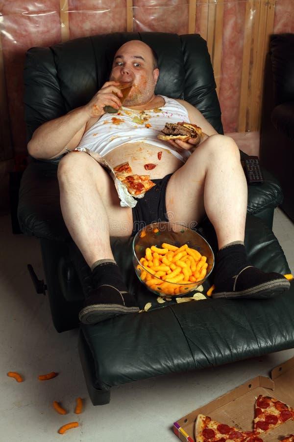 吃汉堡包懒惰土豆的长沙发 库存图片