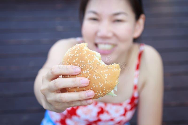 吃汉堡包的妇女 图库摄影