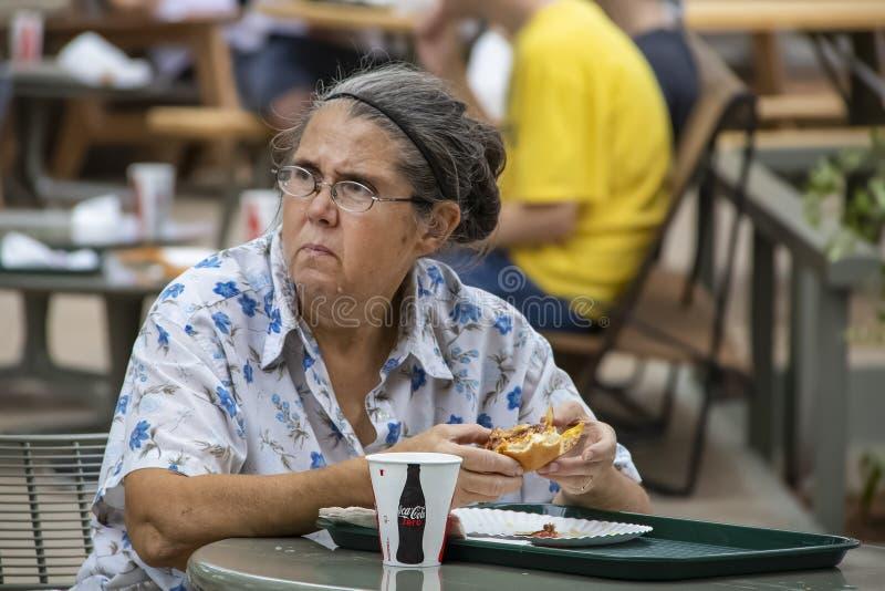 吃汉堡包的老妇人在查寻与在她的面孔的一个不快乐的表示的外部桌上 免版税图库摄影