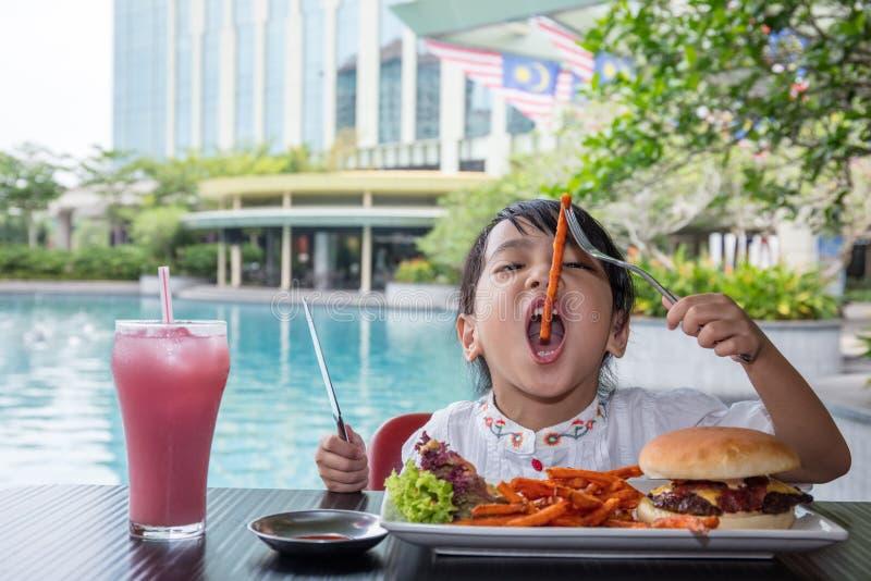 吃汉堡和炸薯条的亚裔矮小的中国女孩 免版税库存图片