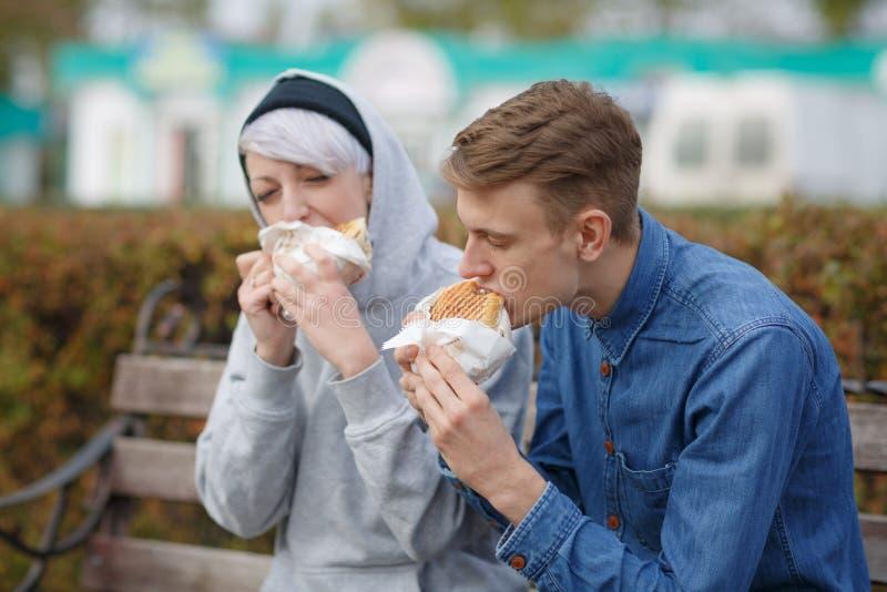 吃汉堡的一对年轻夫妇的画象在长凳的公园 库存照片