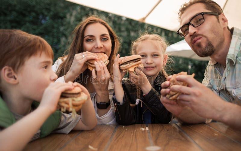 吃汉堡的愉快的家庭坐在咖啡馆的一张桌上 免版税库存照片