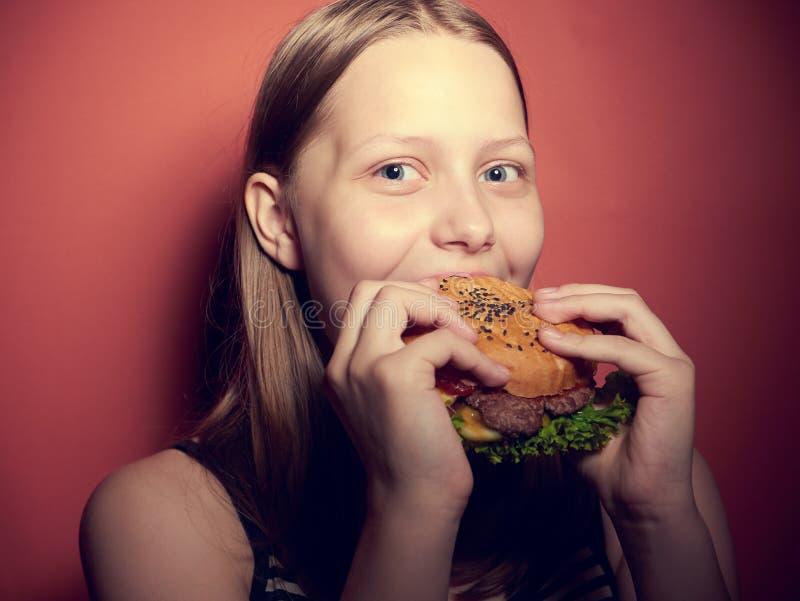 吃汉堡的青少年的女孩 免版税库存图片
