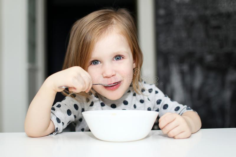 吃汤的可爱的女孩 免版税图库摄影
