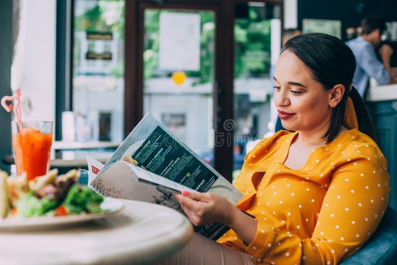 吃沙拉和喝在咖啡馆的愉快的美丽的正大小妇女健康圆滑的人 免版税库存图片