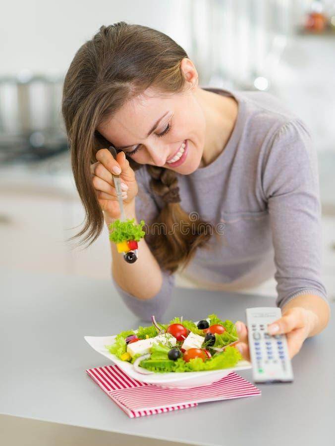 吃沙拉和看电视的笑的妇女 库存图片
