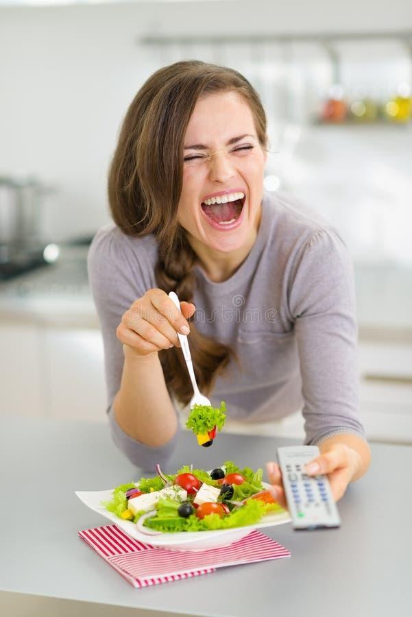 吃沙拉和看电视的笑的妇女 免版税库存照片