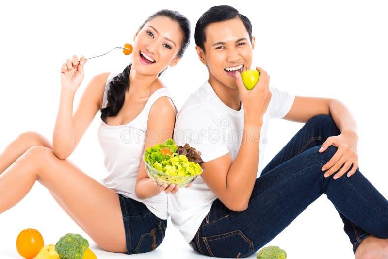 吃沙拉果子的亚洲夫妇 免版税库存图片