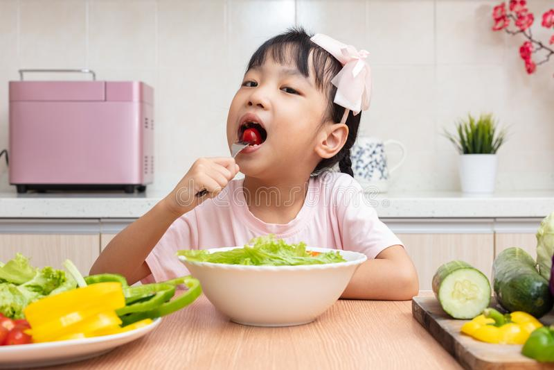 吃沙拉的亚裔中国小女孩在厨房里 库存照片