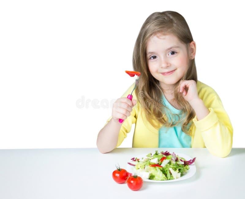 吃沙拉的儿童女孩在白色隔绝的桌上 库存照片