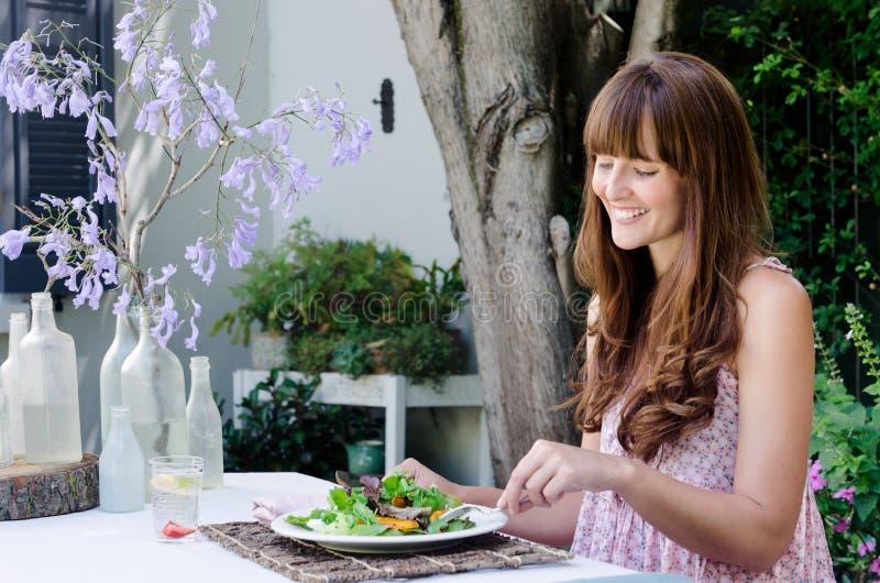 吃沙拉的妇女,在户外用餐 免版税库存照片