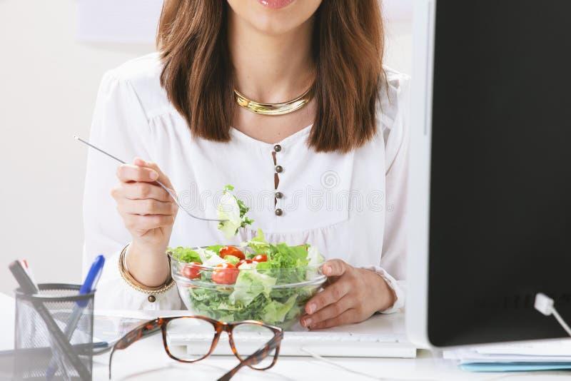 吃沙拉的少妇创造性的设计师在办公室。 免版税库存照片