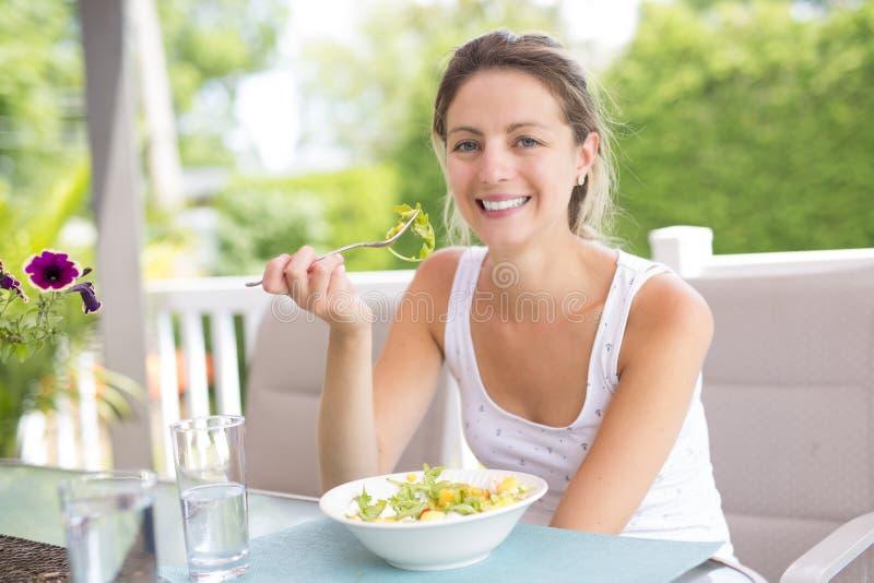吃沙拉的年轻秀丽妇女画象  免版税库存图片
