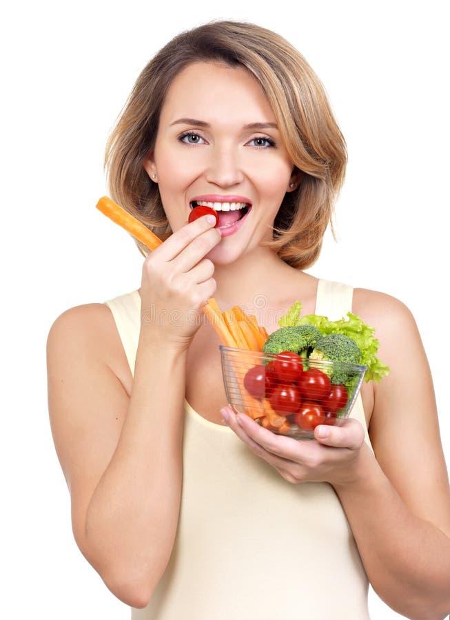 吃沙拉的美丽的年轻健康妇女。 免版税图库摄影