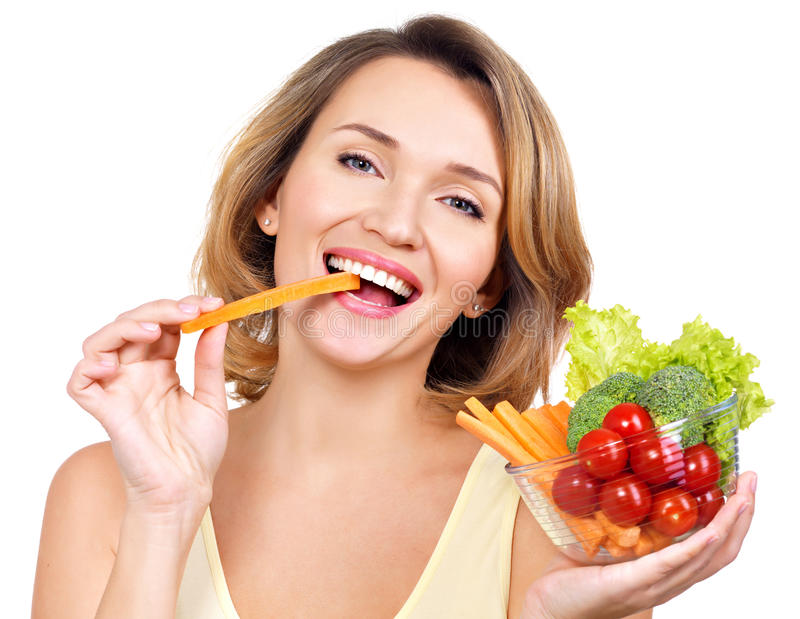 吃沙拉的美丽的年轻健康妇女 免版税库存图片