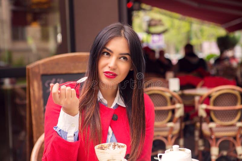 吃沙漠的体贴的妇女在意大利餐馆 免版税库存照片