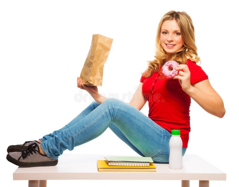 吃油炸圈饼的学校青少年的女孩 免版税图库摄影