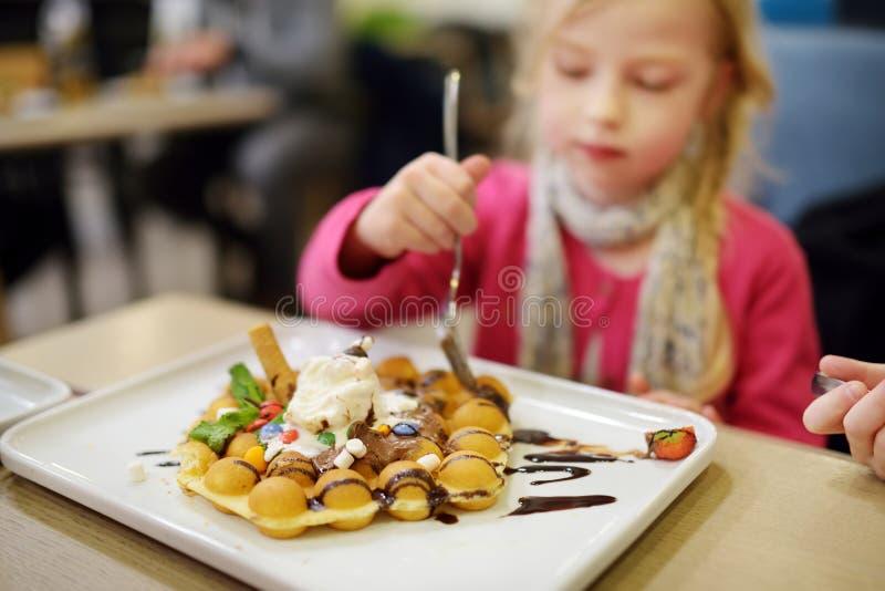 吃泡影奶蛋烘饼用果子、巧克力和蛋白软糖的可爱的小女孩 吃甜点的孩子 库存照片