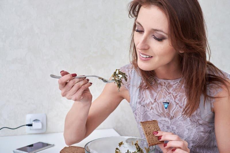 吃海草沙拉的美丽的少妇 在背景空白弓概念节食的显示评定编号附近自己的缩放比例磁带文本附加的空白视窗包裹了您 健康的食物 库存图片