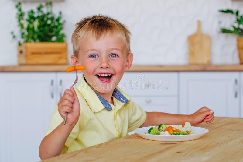 吃混杂的菜沙拉的愉快的小男孩在厨房里 免版税图库摄影