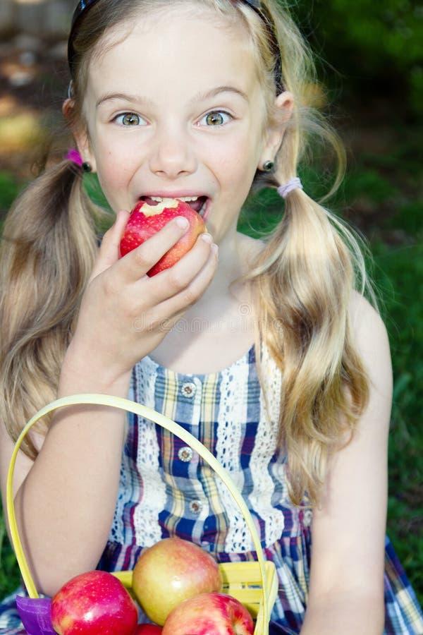 吃滑稽的女孩的苹果 免版税库存照片