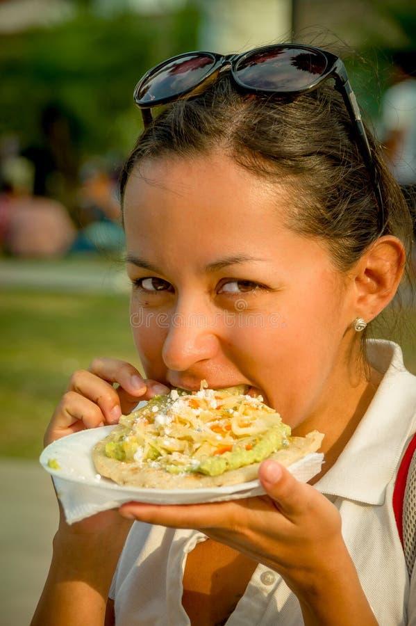 吃炸玉米粉圆饼软的炸玉米饼的美丽的女孩 免版税库存图片