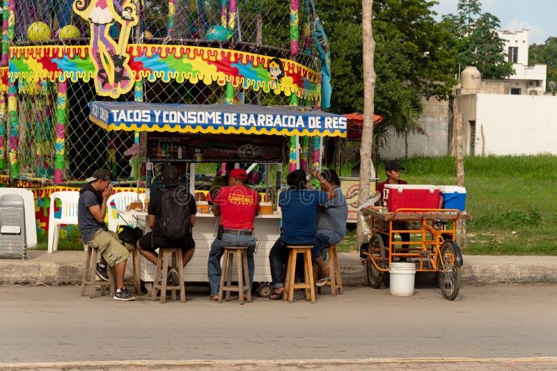 吃炸玉米饼的人们在五颜六色的墨西哥食物停留演出地 免版税库存图片