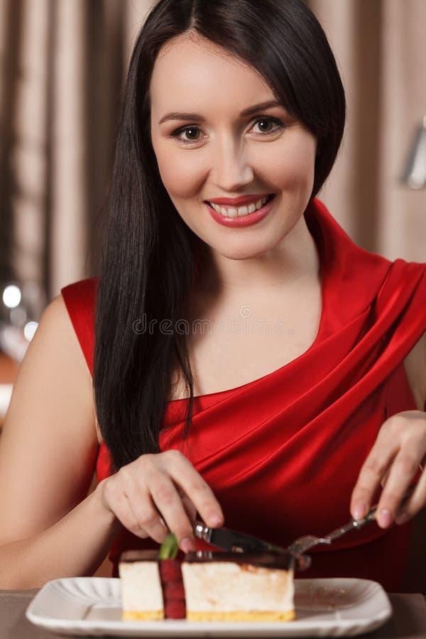 吃点心的妇女。红色礼服的美丽的妇女吃蛋糕a的 库存图片
