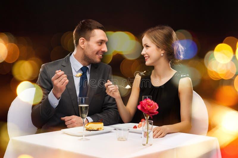 吃点心的微笑的夫妇在餐馆 免版税图库摄影