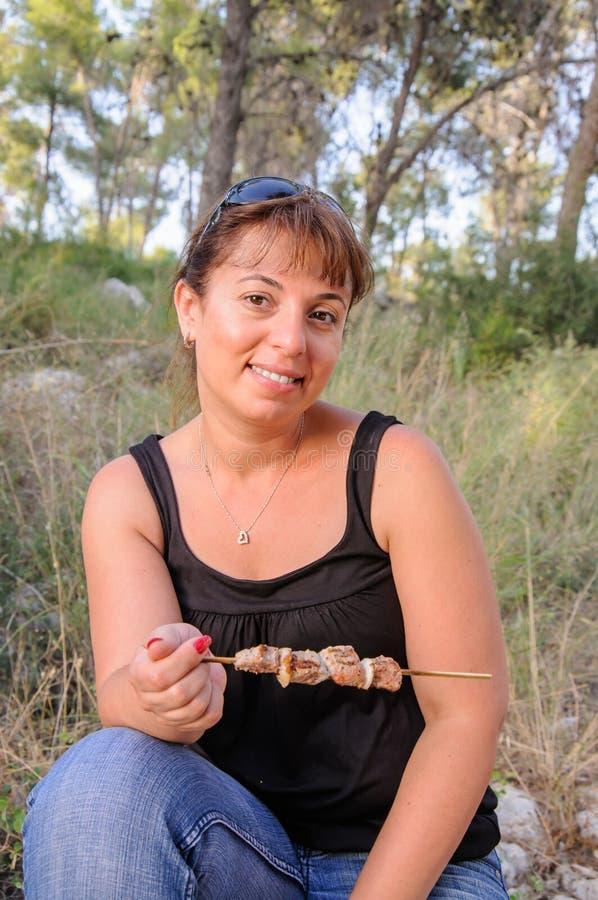 吃烤肉串的妇女 库存照片