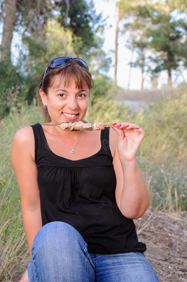 吃烤肉串的妇女 库存图片