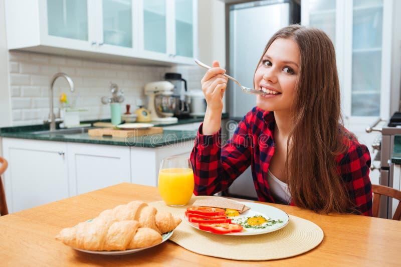 吃煎蛋在厨房的早餐的逗人喜爱的微笑的妇女 库存图片