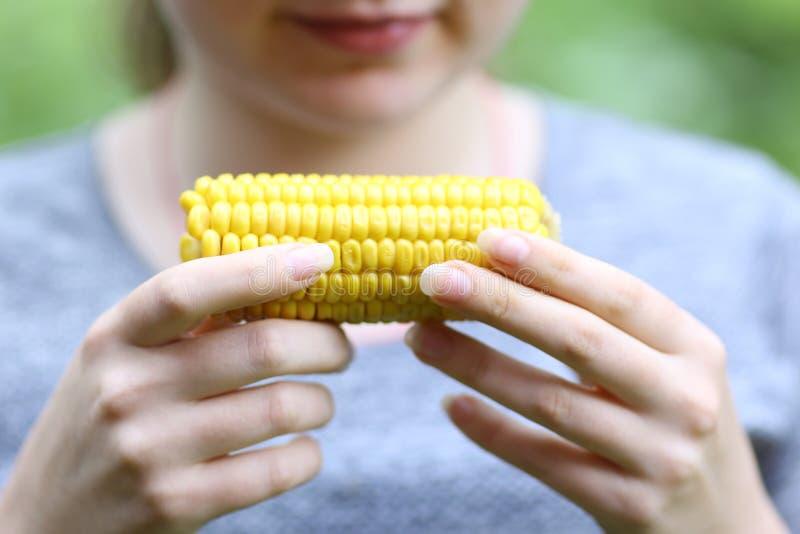 吃煮玉米芯的少女近照 库存照片