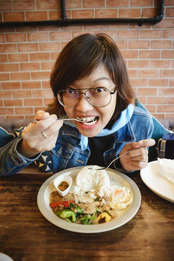吃猪肉炒饭的女孩在餐馆 免版税库存照片