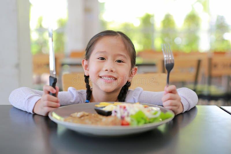 吃猪肉牛排和菜沙拉在桌上的愉快的亚裔儿童女孩画象与藏品刀子和叉子 有的孩子 库存照片