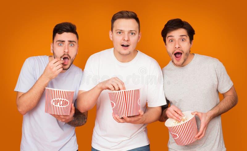 吃玉米花和电影的感兴趣的朋友 免版税库存图片