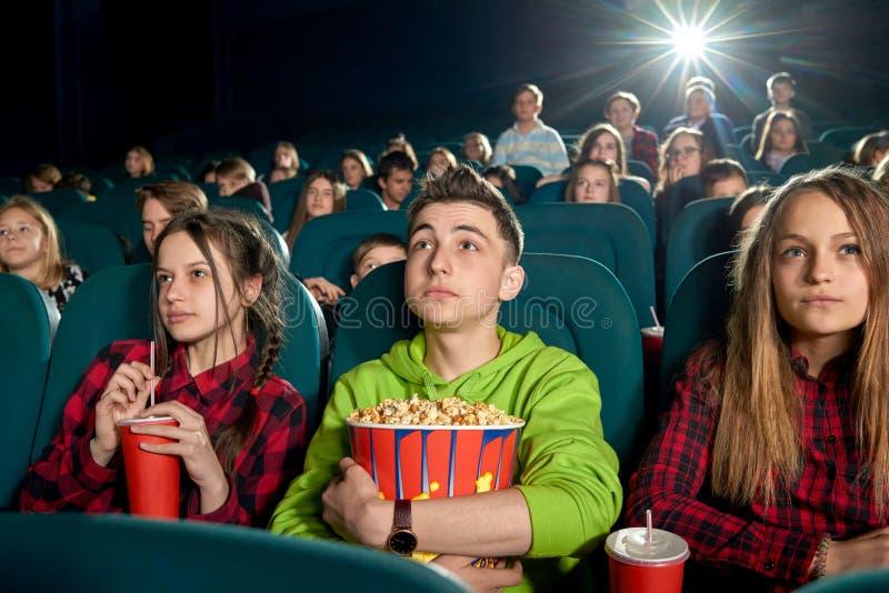 吃玉米花和观看在戏院的少年影片 库存图片