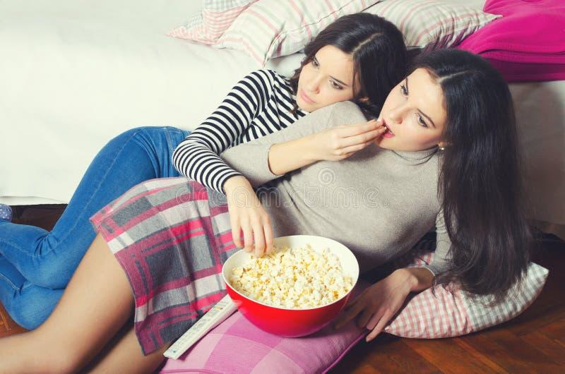 吃玉米花和观看电影的两个美丽的十几岁的女孩 免版税库存图片