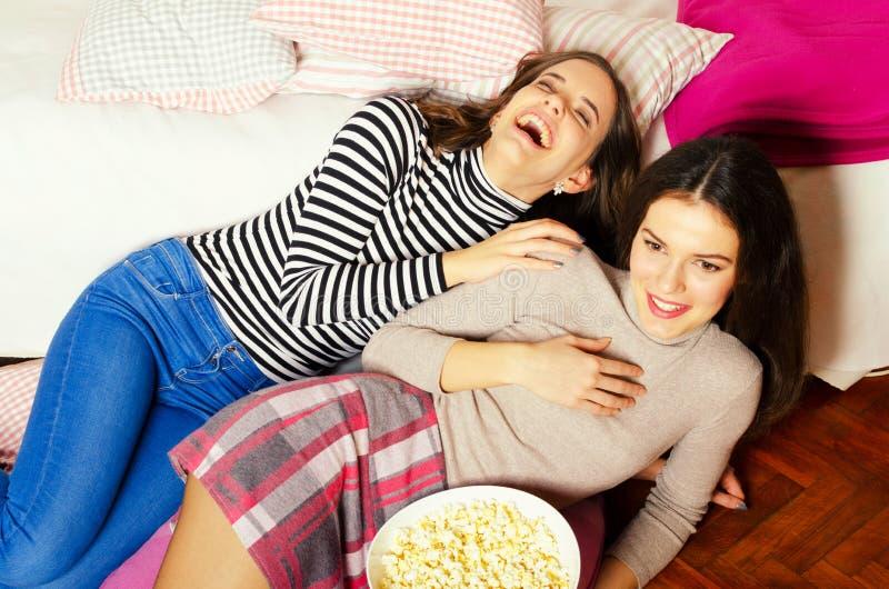 吃玉米花和观看电影的两个美丽的十几岁的女孩 库存图片