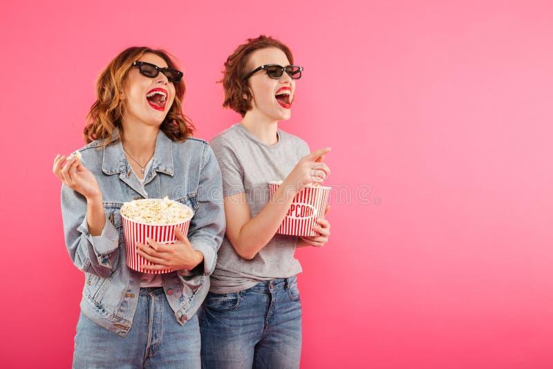 吃玉米花手表影片的笑的妇女朋友 免版税图库摄影